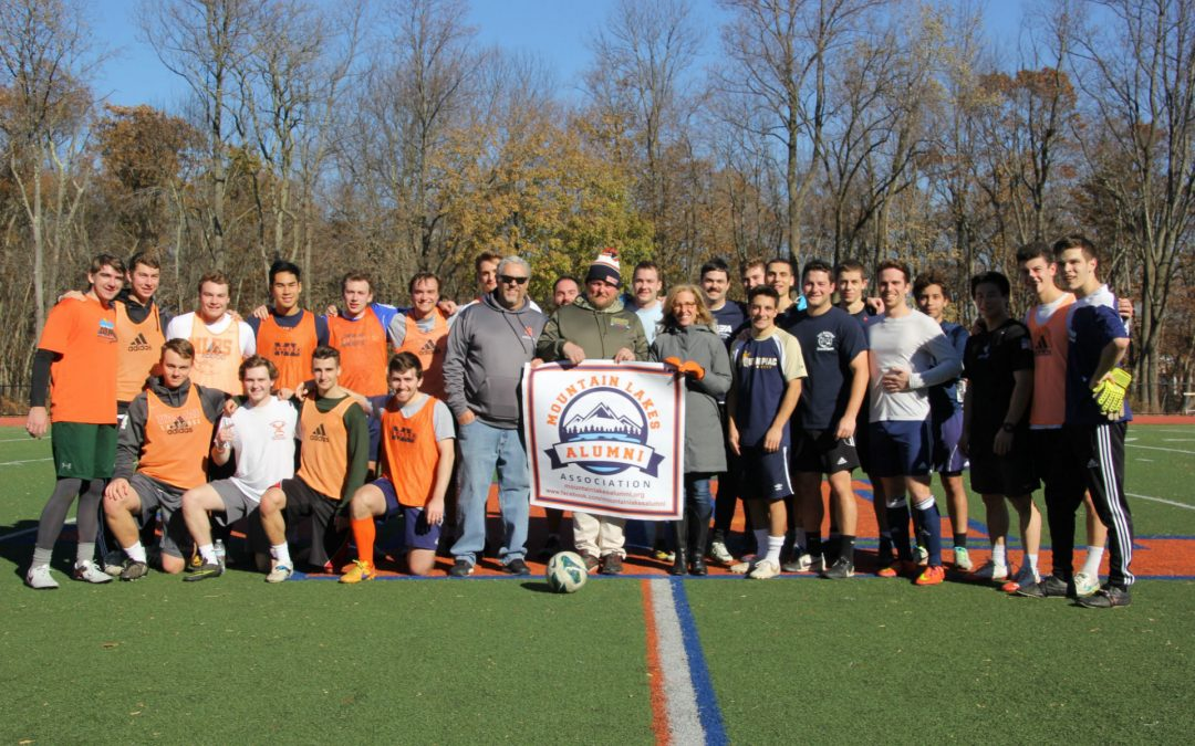 MLAA reps and alumni players pose on the field following the 2017 Mountain Lakes Alumni soccer game.